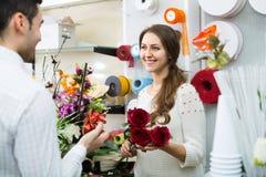 Человек цветков продавца женщины предлагая Стоковая Фотография