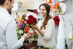 Человек цветков продавца женщины предлагая Стоковое Изображение
