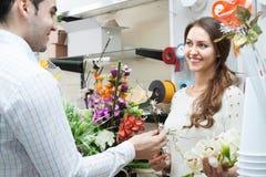 Человек цветков продавца женщины предлагая Стоковая Фотография RF