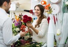 Человек цветков продавца женщины предлагая Стоковое Фото