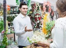 Человек цветков продавца женщины предлагая Стоковые Фотографии RF