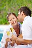Человек целуя женщину с шампанским на бассейне Стоковое фото RF
