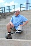 Человек человека с ампутированной конечностью усаженный с ногой и протезом пересек, рука на бедре стоковые изображения rf