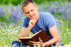 Человек читает книгу в поле Стоковые Фотографии RF