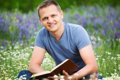 Человек читает книгу в поле Стоковые Изображения