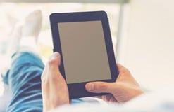 Человек читая книгу на цифровом приборе стоковые фото