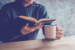 Человек читая книгу с выпивая кофе или чаем стоковые фотографии rf