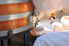 Человек льет мед от бочонка стоковые изображения rf