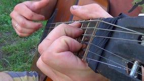 Человек элегантный общипывает строки, играя гитару на естественной предпосылке акции видеоматериалы