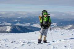 Человек Backpacker представляет в горах зимы Стоковые Фото