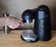 Человек Barista подготавливает кофе в машине кофе на деревянной предпосылке Стоковое фото RF