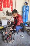 Человек Bayi делая серебряный бак Heqing известно для продукции artigianal серебряных инструментов Стоковая Фотография