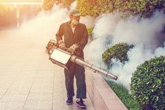 Человек fogging для того чтобы исключить москита для предотвращает тропическую лихорадку распространения стоковые фото