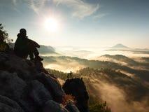 Человек Hiker принимает остатки на горном пике Человек кладет на саммит, долину осени мембраны стоковые фотографии rf