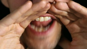 Человек screams в камеру на черной предпосылке Рот и конец-вверх оскала сток-видео