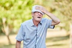 Человек Seniorfainting охлаждая его голову стоковые фото