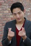 Человек Smiley азиатский делая знак сердца пальца Корейский знак пальца сердца Стоковая Фотография RF