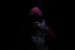 Человек Vaping держа mod Облако пара Черная предпосылка Vaping электронная сигарета с много дымом Стоковое Фото