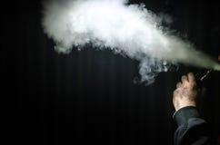 Человек Vaping держа mod Облако пара Черная предпосылка Vaping электронная сигарета с много дымом Стоковые Изображения