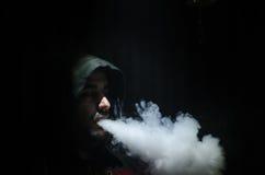 Человек Vaping держа mod Облако пара Черная предпосылка Vaping электронная сигарета с много дымом Стоковая Фотография RF
