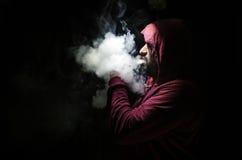 Человек Vaping держа mod Облако пара Черная предпосылка Vaping электронная сигарета с много дымом Стоковые Фотографии RF