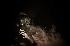 Человек Vaping держа mod Облако пара Черная предпосылка Vaping электронная сигарета с много дымом Стоковые Фото