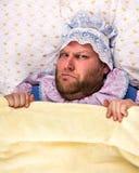 Человек weared как младенец сердитый в кровати стоковая фотография rf