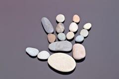 Человеческая ладонь отлично идет из малых камней моря Стоковая Фотография