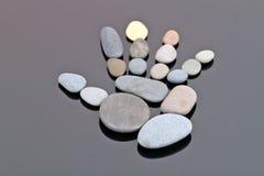 Человеческая ладонь отлично идет из малых камней моря Стоковое Фото