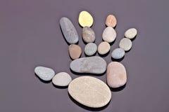 Человеческая ладонь отлично идет из малых камней моря Стоковые Изображения RF
