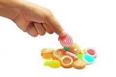 Человеческая рука - выберите вверх конфету студня сладостную изолированную на белизне Стоковое Изображение RF