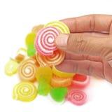Человеческая рука - выберите вверх конфету студня сладостную изолированную на белизне Стоковые Изображения