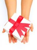 Человеческая рука держа красный подарок смычка Стоковые Фотографии RF