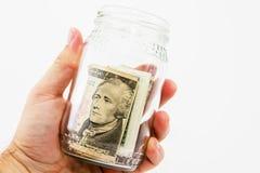 Человеческая рука держа сбережения раздражает с деньгами США с простой предпосылкой Стоковые Фото