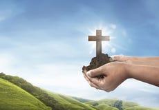 Человеческая рука держа христианский крест с почвой на руке Стоковая Фотография RF