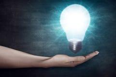 Человеческая рука держа электрическую лампочку lego руки творческих способностей принципиальной схемы здания вверх по стене Стоковые Изображения