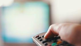 Человеческая рука изменяет каналы на дистанционное управление ТВ видеоматериал