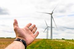 Человеческая рука направляя к турбинам энергии ветра производит электричество стоковое изображение