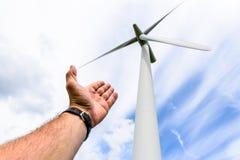 Человеческая рука направляя к турбинам энергии ветра производит электричество стоковая фотография rf