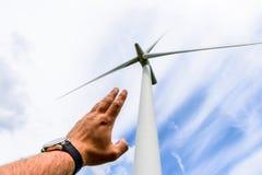 Человеческая рука направляя к турбинам энергии ветра производит электричество стоковое изображение rf