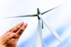 Человеческая рука направляя к турбинам энергии ветра производит электричество стоковое фото rf