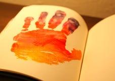 Человеческая рука покрашенная на тетради стоковые фото