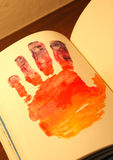 Человеческая рука покрашенная на тетради Стоковое фото RF