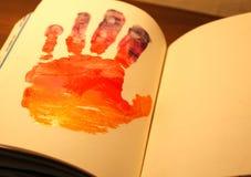 Человеческая рука покрашенная на тетради Стоковая Фотография RF