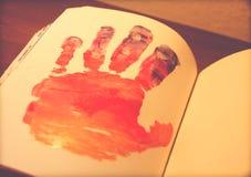 Человеческая рука покрашенная на тетради стоковые фотографии rf