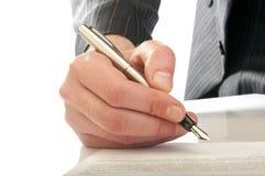 Человеческая рука с ручкой делает подпись Стоковая Фотография