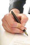 Человеческая рука с ручкой делает подпись Стоковые Фотографии RF