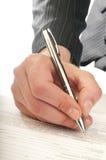 Человеческая рука с ручкой делает подпись Стоковое Изображение