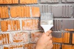 Человеческая рука с серым цветом покрасила кирпичную стену картины щетки Стоковое Фото
