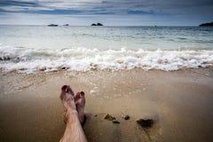 Человеческие ноги на пляже волны волны океана переднего плана фокуса стоковые фотографии rf
